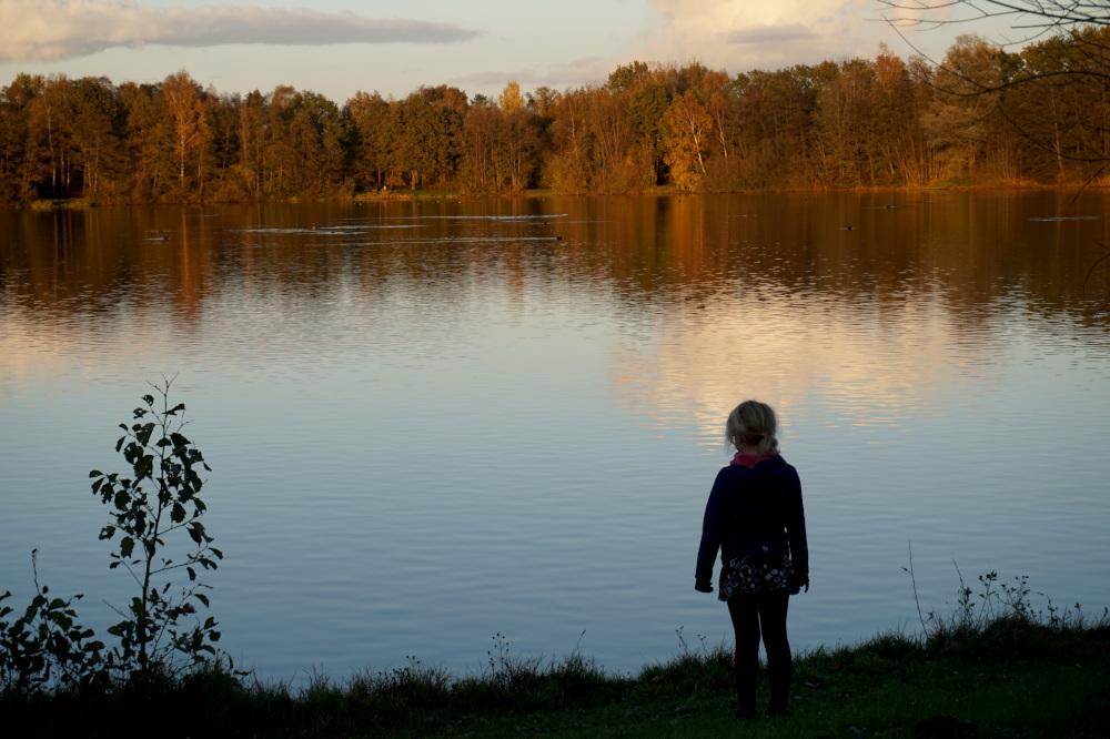 Man sieht an einem sonnigen Herbsttag ein Mädchen auf den See schauen.